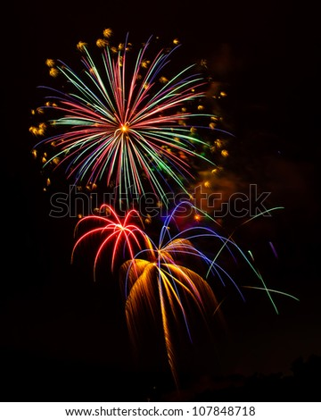 Holiday Celebration Fireworks Display - Exploding fireworks light up the night sky in a beautiful pyrotechnic display. - stock photo