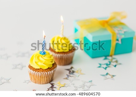 holiday, celebration, greeting and party concept - birthday cupcakes with burning candles and present