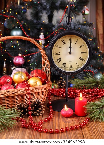 Holiday composition with Christmas decorations, candles and clocks  on the background of a decorated christmas tree