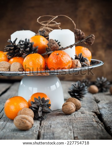 Holiday Composition with Tangerines, Pine cones, Walnuts on Wooden Background, holiday decoration