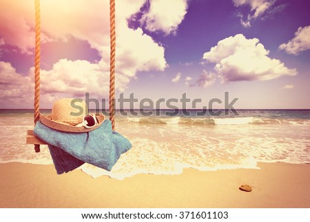 Holiday concept with idyllic beach scene with sunhat and glasses on swing - vintage tone effect for a nostalgic feel