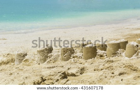 Holiday concept with sandcastles on the seaside - stock photo