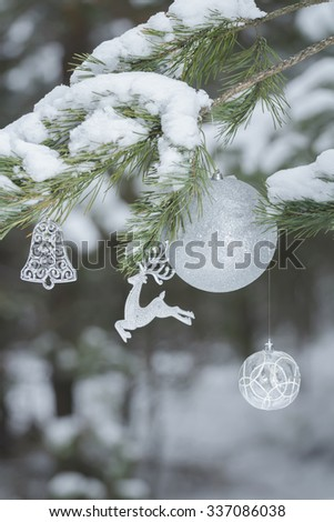 Holiday conifer tree branches with Santa Claus's reindeer ornament and Christmas baubles at snowy wood background  - stock photo