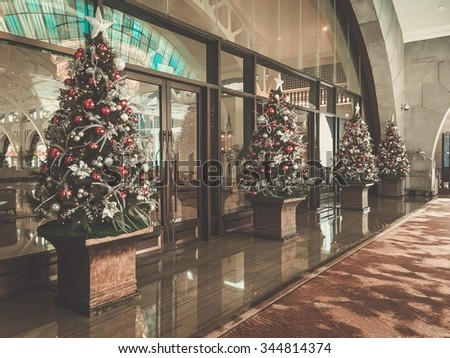 Holiday decorated christmas tree front entrance to commercial building.  - stock photo