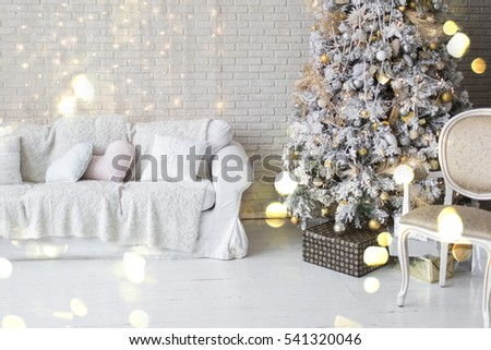 holiday decorated room with christmas tree and armchair with blanket white interior with lights