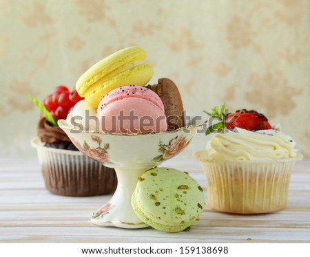 holiday desserts, cupcakes and macaroons on a vintage background - stock photo