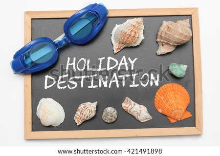 Holiday Destination text on chalk board with swimming goggle and shell - vacation and business concept - stock photo