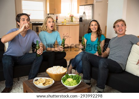 Holiday event at home a group of people watching tv at home celebrating - stock photo