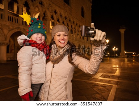 Holiday family trip to Venice, Italy can change the whole Christmas experience. Happy mother and child in funny Christmas hat taking photos on Piazza San Marco in the evening
