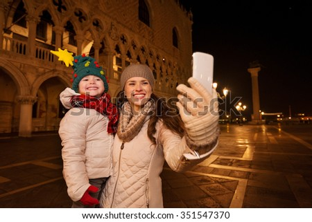Holiday family trip to Venice, Italy can change the whole Christmas experience. Happy mother with child taking selfie with smartphone while standing on Piazza San Marco in the evening. Winter Tourism