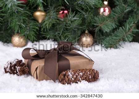 Holiday gift box and pine cones on snow with Christmas tree in background - stock photo