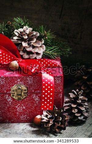 Holiday gift box decorated with red ribbon, pine cones, fir branches, Christmas balls and nuts, toned image, selective focus