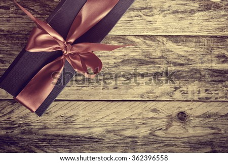 holiday gift box with ribbon on old wooden table, retro style, sepia toned - stock photo