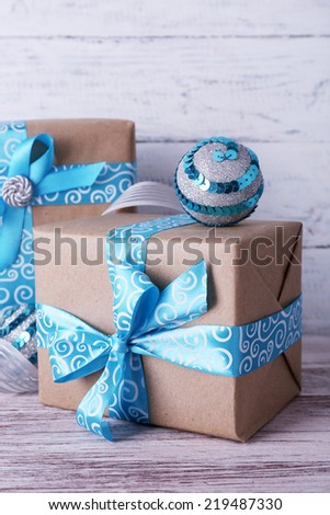 Holiday gift boxes decorated with blue ribbon on table on wooden wall background - stock photo