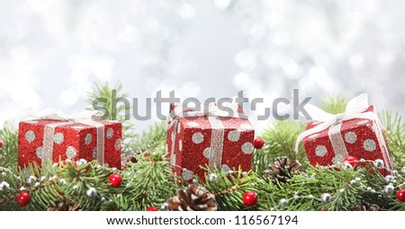 Holiday gift boxes with fir branch on abstract background. - stock photo