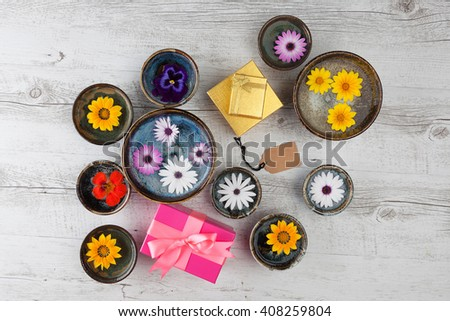Holiday gifts concept with flowers, gift boxes, and empty tag. Top view with copy space. - stock photo