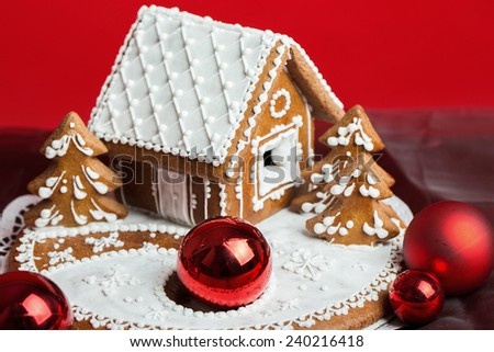 Holiday Gingerbread house on red background, christmas cookie - stock photo