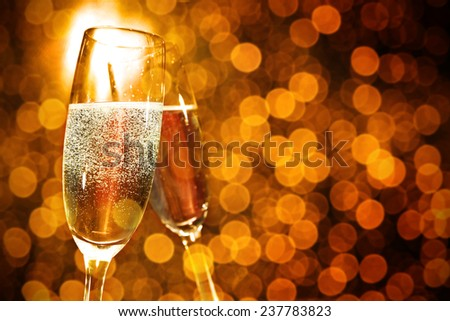 holiday golden background and glasses of champagne