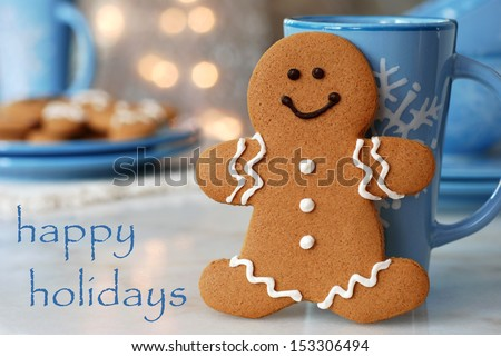 Holiday greeting card with smiling gingerbread man standing next to snowflake mug.  Plate of additional cookies and defocused holiday lights in background.   - stock photo