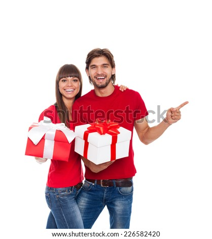 holiday happy couple hold present gift box point finger to empty copy space wear red shirt, man and woman love smile embracing, isolated over white background - stock photo