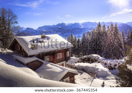 Holiday home in the winter with snow covering the landscape in the swiss mountains with view on a distant mountain range - stock photo