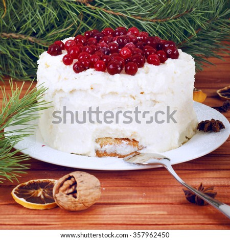 Holiday layered cake with cream and cranberry decoration under christmas tree