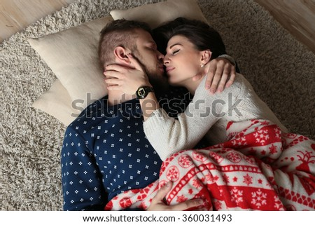 holiday photo of beautiful tender couple in warm clothes, posing in cozy room