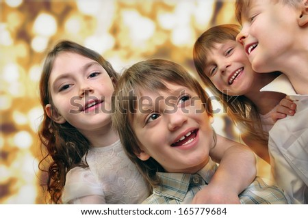 Holiday portrait of happy children against bright golden background. Studio shot.