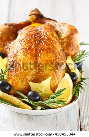 Holiday roasted lemon chicken with fruit garnish. - stock photo