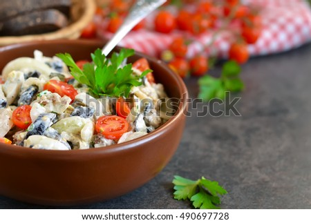 Holiday salad with mushrooms, tomatoes and sauce on a black background.
