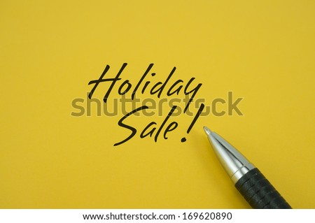 Holiday Sale! note with pen on yellow background