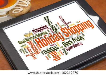 holiday shopping word cloud on a digital tablet with a cup of tea and cookie