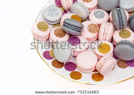 Holiday sparkling macaron cookies on a white plate. Closeup, isolated on white.
