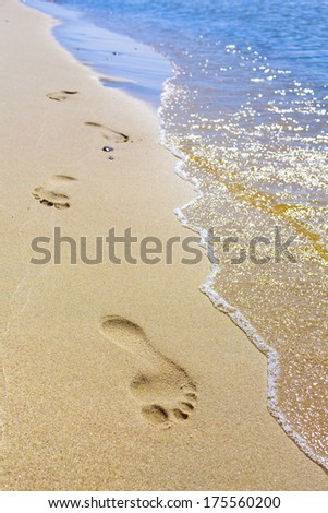 Holiday symbol of quiet rest in attractive areas on the beach, with visible footprints in the sand. - stock photo