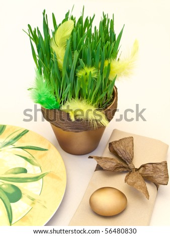 holiday table serving with golden egg and green grass