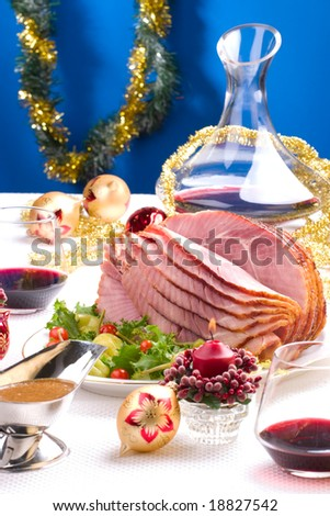 Holiday table setting with delicious whole baked sliced ham, marinated peppers, cherry tomatoes, vegetable salad and glasses of red wine. Christmas decoration, candles, ornaments around. - stock photo