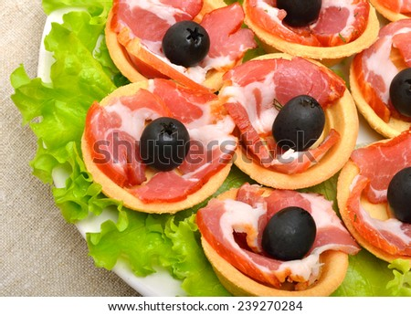 Holiday tartlets stuffed with ham, olives and green lettuce  on white plate on the tablecloth - stock photo