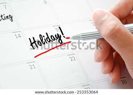 Holiday text on the calendar (or desk planner) underlined with red marker - stock photo