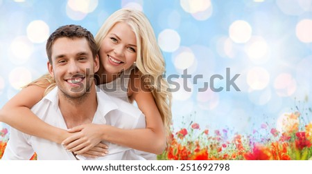 holiday, valentine's day, dating and love concept - happy couple having fun over blue lights and poppy field background - stock photo
