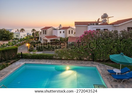 Holiday villas with pool in sunset light - stock photo