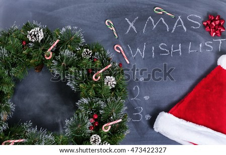 Holiday Wreath, Santa cap, gift bow and candy canes on erased chalkboard with Christmas wish list written on board.