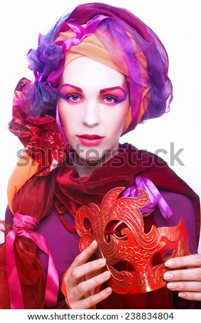 Holiday. Young woman in bright turban posing with red mask - stock photo