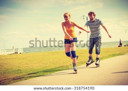 Holidays, active people and friendship concept. Young fit couple on roller skates riding outdoors on sea shore, woman and man rollerblading together on the promenade - stock photo