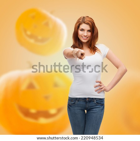 holidays, advertisement, gesture and people concept - smiling young woman in blank white t-shirt pointing finger at you over halloween pumpkins background - stock photo