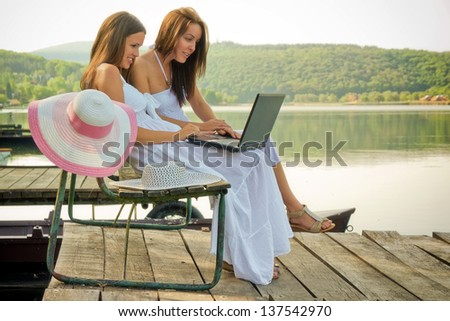 Holidays and internet / Two young woman are sitting on a pier and use theirs laptop to surfing on the internet - stock photo