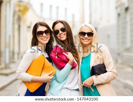 holidays and lifestyle concept - beautiful girls with bags in the ctiy - stock photo