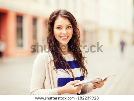 holidays and tourism concept - beautiful girl looking into tourist book in the city