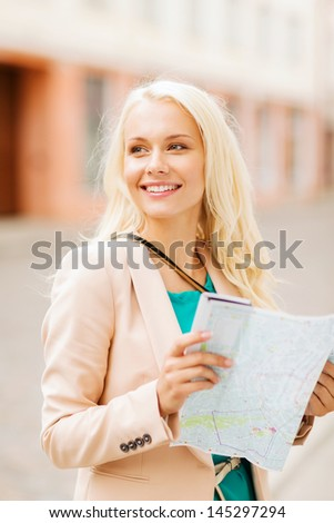 holidays and tourism concept - beautiful girl looking into tourist map in the city - stock photo