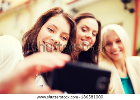holidays and tourism concept - beautiful girls taking selfie in cafe in city - stock photo