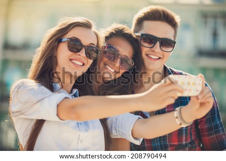 holidays and tourism, modern technology concept - beautiful friends taking picture in the city - stock photo